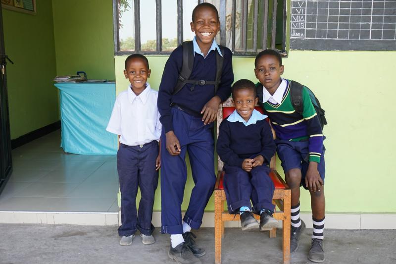 Denis, David, Pastor und Meteli in ihren Schuluniformen